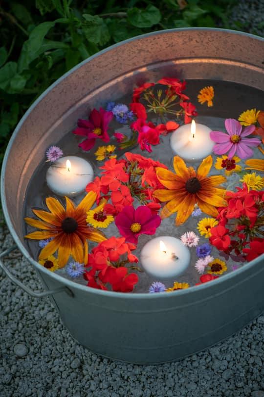 Ein Kessel mit Schwimmkerzen und farbenprächtigen Sommerblumen