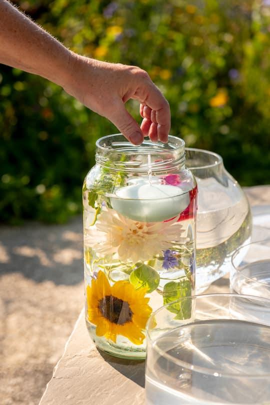 Hohes Glas mit Blumen und Schwimmkerzen