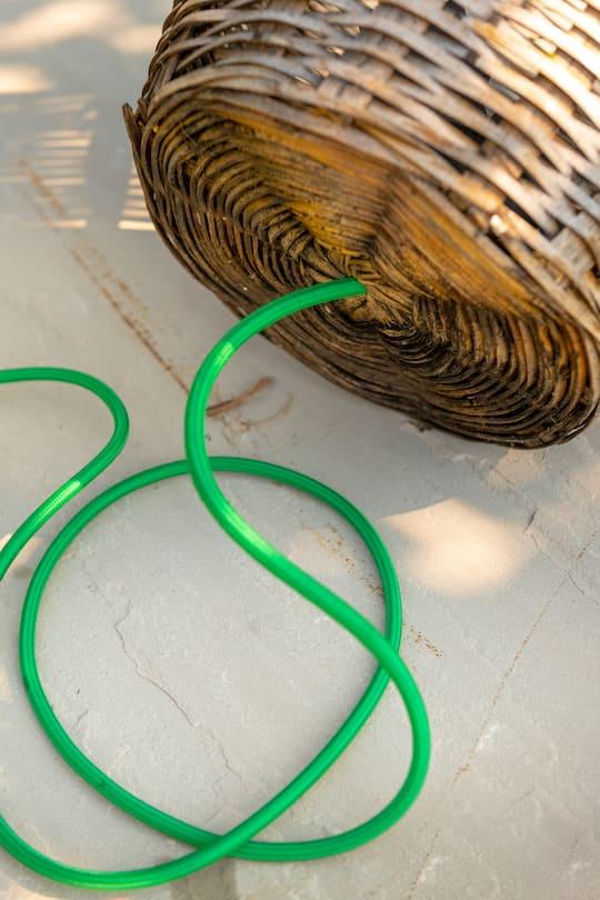 Korb mit Loch, durch das ein grünes Kabel gezogen wird