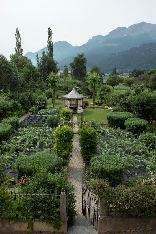 Blick vom Devon House in Poschiavo GR hinunter auf den Garten mit dem Pavillon