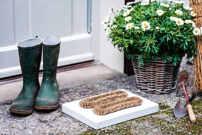 Fussabtreter mit Gummistiefel, Blumen im Topf und Gartenhacken