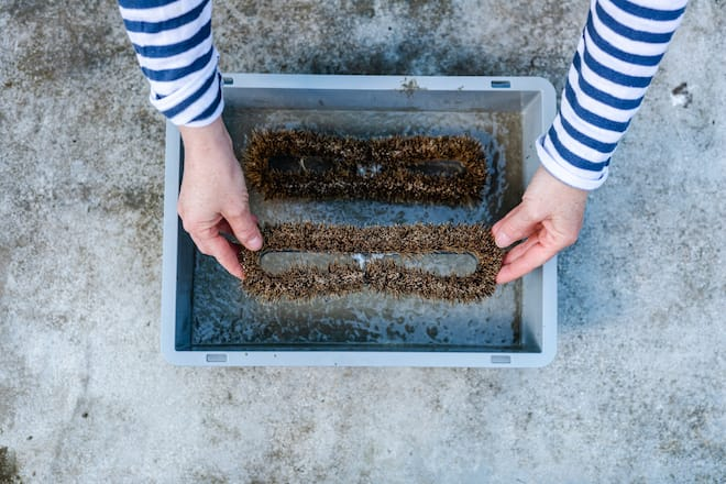 Sandra Dangel drückt zwei Bürsten in die Betonmasse