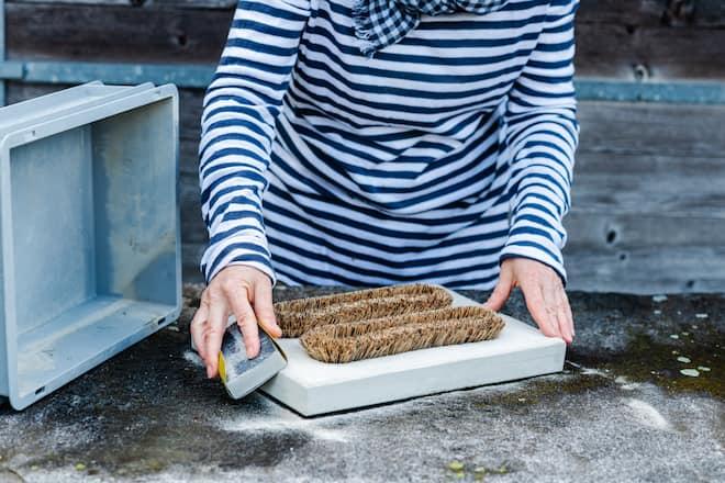 Sandra Dangel schleift die Oberfläche des Fussabstreifers ab