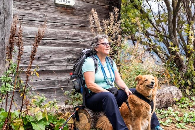Christine Nydegger und Mischlingshündin Tapas gönnen sich eine Pause auf einem Baumstamm