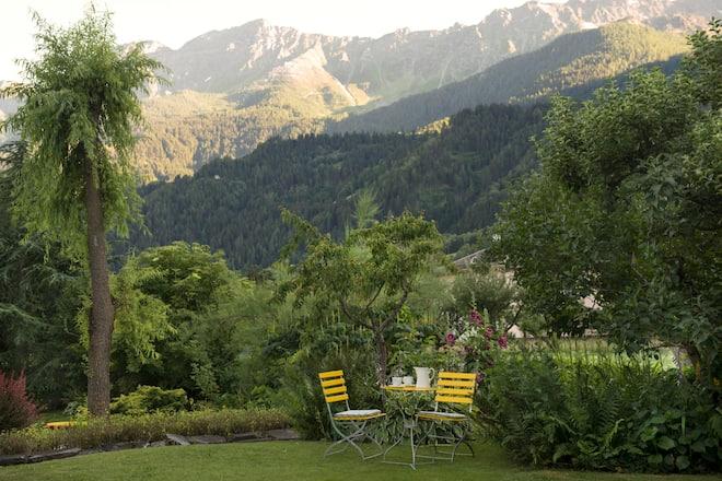 Garten des Devon House in Poschiavo GR mit Gartentisch und -stühlen und Blick auf die Berge
